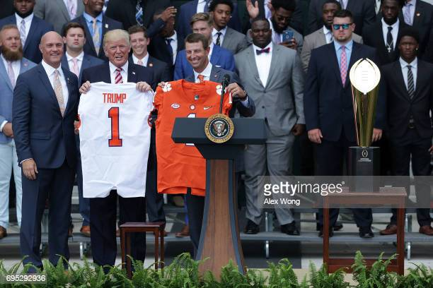 Clemson University President Jim Clements and Clemson Tigers head coach Dabo Swinney present two jerseys one for President Donald Trump and one for...