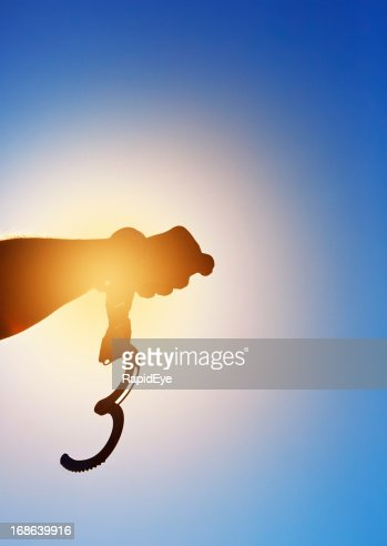 Clenched fist with single, open handcuff silhouetted against the sun
