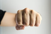 Close up image of a white male's single clenched fist punching towards the viewer or frame. No rings or markings on the man's hand. Copy space area for crime or fear based concepts and ideas. White ba