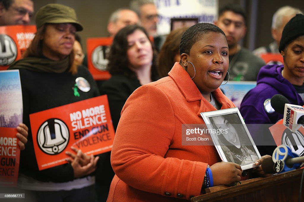 Cleopatra Cowley-Pendleton holds a picture of her daughter Hadiya, 15, while speaking at a gathering of gun violence victims and gun control advocates at Cornell Square Park on the anniversary of the Sandy Hook Elementary School shooting December 14, 2013 in Chicago, Illinois. Thirteen people, including a three-year-old boy, were wounded when gunmen opened fire on a crowd gathered at the basketball courts in Cornell Square Park in September. Twenty children and 6 adults were killed when a gunman opened fire at Sandy Hook School. Hadiya was shot and killed while hanging out with friends in a park after school on January 29, 2013, one week after performing at President Barack Obamas second inauguration. Hadiya is 1 of more than 400 people who have been murdered in Chicago so far this year, most by gunfire.