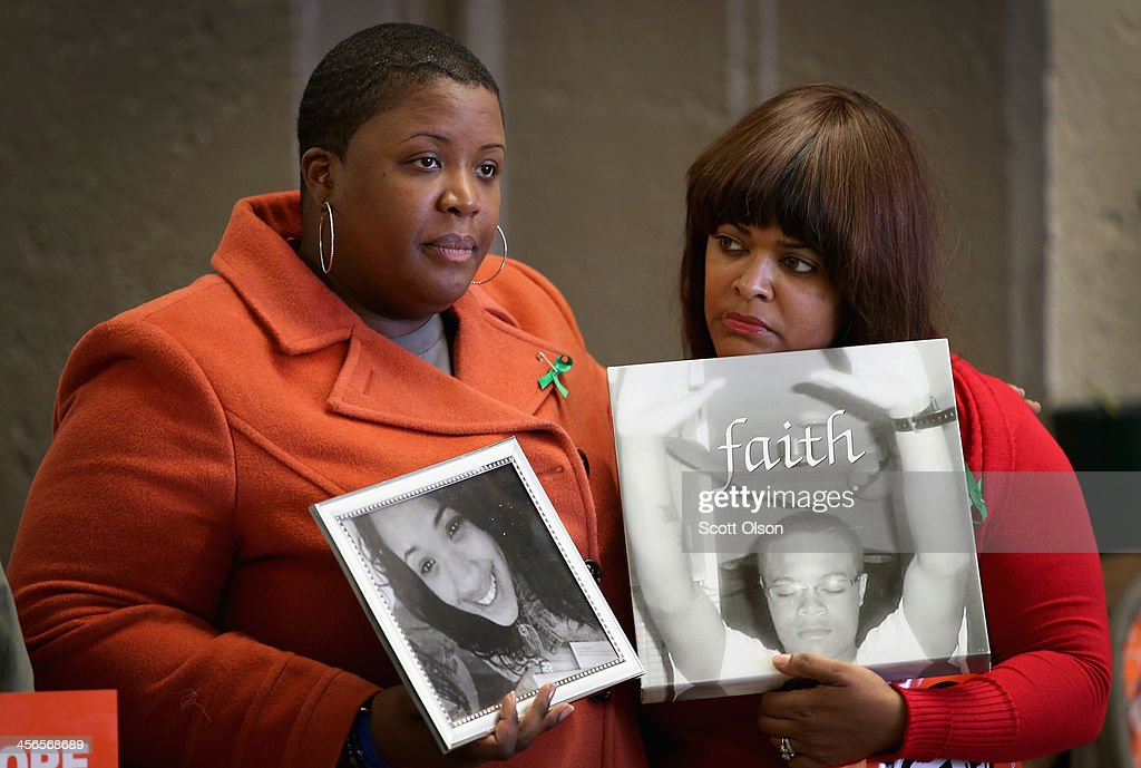 Cleopatra Cowley-Pendleton (L) holds a picture of her daughter Hadiya, 15, while standing with Shundra Robinson who is holding a picture of her son Deno Wooldridge, 18, during a gathering of gun violence victims and gun control advocates at Cornell Square Park on the anniversary of the Sandy Hook Elementary School shooting December 14, 2013 in Chicago, Illinois. Thirteen people, including a three-year-old boy, were wounded when gunmen opened fire on a crowd gathered at the basketball courts in Cornell Square Park in September. Twenty children and 6 adults were killed when a gunman opened fire at Sandy Hook School. Hadiya was shot and killed while hanging out with friends in a park after school on January 29, 2013, one week after performing at President Barack Obamas second inauguration. Wooldridge was shot and killed while standing on his grandmother's porch on October 18, 2010. More than 400 people have been murdered in Chicago so far this year, most by gunfire.