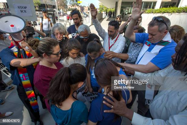 Clergy and activists prayer over daughters and nieces of Romulo AvelicaGonzalez as family members rally for his release outside US Immigration and...