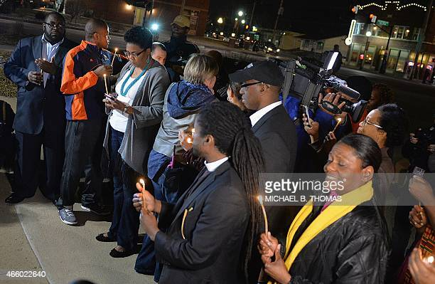Clergy and other religious leaders participate in a candlelight memorial vigil near the the Ferguson Police Department in Ferguson Missouri on March...