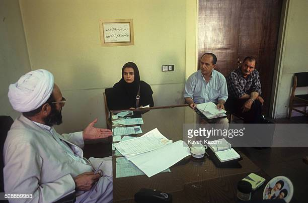 A clergy judge examines the case of a couple wishing to divorce in the court In Iran most administrative offices dealing with weddings and divorces...