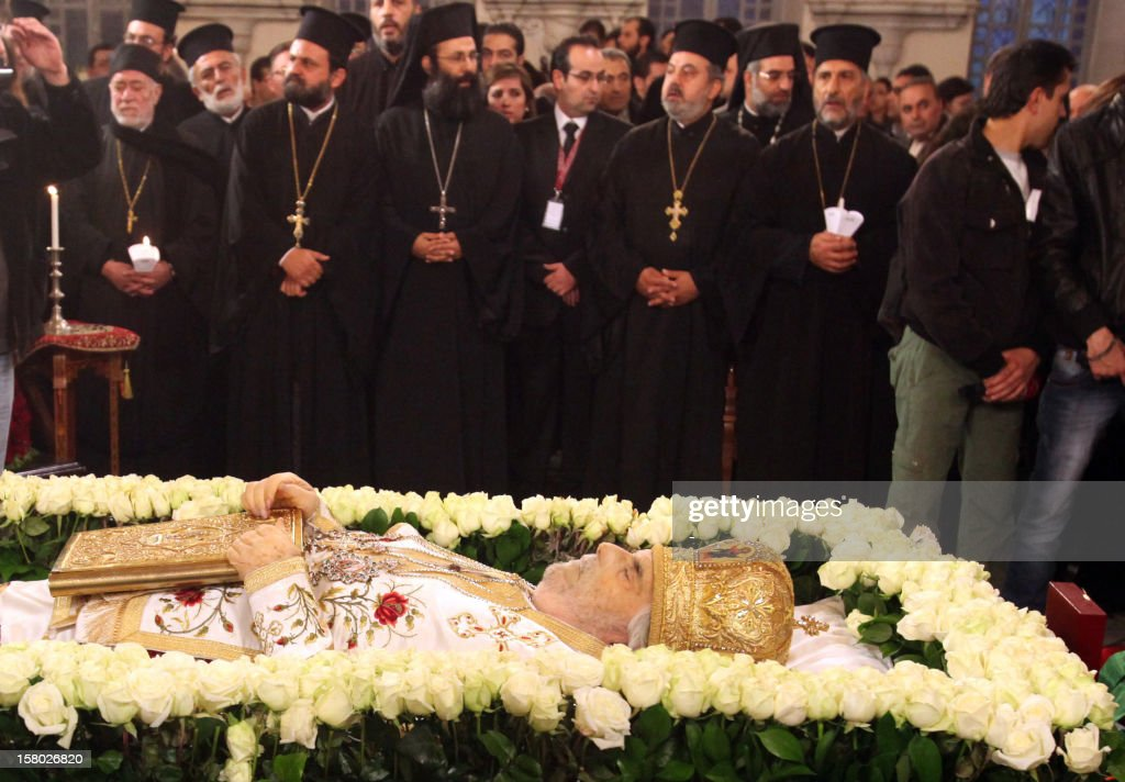 Clergy stand by the body of Greek Orthodox Patriarch of Syria Ignatius IV Hazim, is layed out at the Mariamite Cathedral of Damascus, on December 9, 2012. Patriarch Hazim died in neighboring Beirut, Lebanon, of a stroke on December 5, and his body has been taken to Syria for burial on December 10. AFP PHOTO/STR