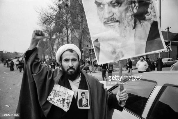 A clergyman decorated with a banner of Ayatollah Khomeini and his pictures pinned on hishabit demonstrates in Tehran during the Iranian Revolution...