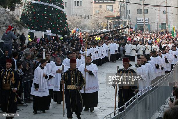 Clergymen march in Manger Square outside the Church of the Nativity as Christians gather for Christmas celebrations in the West Bank city of...