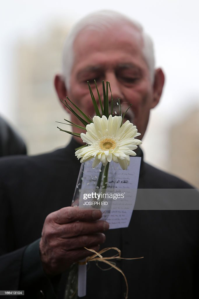 A cleric holds a flower during a gathering of clerics representing the various Lebanese religious communities for peace in central Beirut on the eve of the anniversary of the 1975-1990 civil war on April 12, 2013. AFP PHOTO/JOSEPH EID