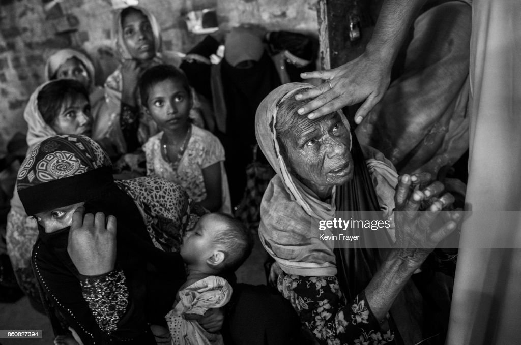 COX'S BAZAR, BANGLADESH - SEPTEMBER 22: A cleric touches the head of a Rohingya refugee woman as she asks for food as they rest in an Islamic school or madrassa after arriving by boat on the Bangladesh side of the Naf River at Shah Porir Dwip after fleeing their villages in Myanmar, on September 22, 2017 in Cox's Bazar, Bangladesh. More than half a million Rohingya refugees have flooded into Bangladesh to flee an offensive by Myanmar's military that the United Nations has called 'a textbook example of ethnic cleansing'. The refugee population is expected to swell further, with thousands more Rohingya Muslims said to be making the perilous journey on foot toward the border, or paying smugglers to take them across by water in wooden boats. Hundreds are known to have died trying to escape, and survivors arrive with horrifying accounts of villages burned, women raped, and scores killed in the 'clearance operations' by Myanmar's army and Buddhist mobs that were sparked by militant attacks on security posts in Rakhine state on August 25, 2017. What the Rohingya refugees flee to is a different kind of suffering in sprawling makeshift camps rife with fears of malnutrition, cholera, and other diseases. Aid organizations are struggling to keep pace with the scale of need and the staggering number of them - an estimated 60 percent - who are children arriving alone. Bangladesh, whose acceptance of the refugees has been praised by humanitarian officials for saving lives, has urged the creation of an internationally-recognized 'safe zone' where refugees can return, though Rohingya Muslims have long been persecuted in predominantly Buddhist Myanmar. World leaders are still debating how to confront the country and its de facto leader, Aung San Suu Kyi, a Nobel Peace Prize laureate who championed democracy, but now appears unable or unwilling to stop the army's brutal crackdown.