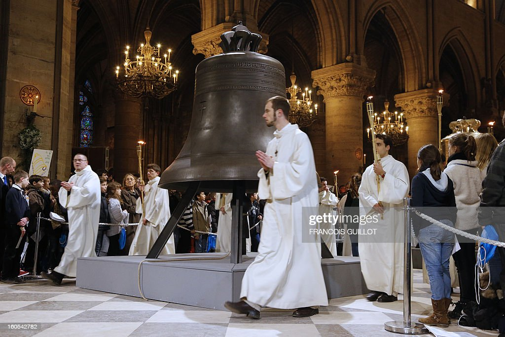 Clerics walk by the new bells of Notre-Dame de Paris Cathedral during their blessing mass on February 2, 2013 in Paris. The bell on the picture, the biggest among the nine new ones, has been made in the Dutch Royal Eijbouts foundry in Asten. Baptised 'Marie,' it weighs 6 tons and plays a G sharp note (sol diese).