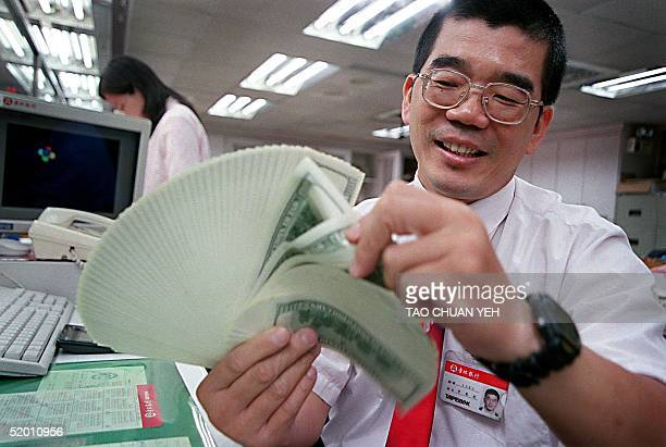 A clerk at a local bank counts US dollar bills in Taipei 19 July 1999 as demand for US currency rose on concerns over escalating crossstrait tensions...