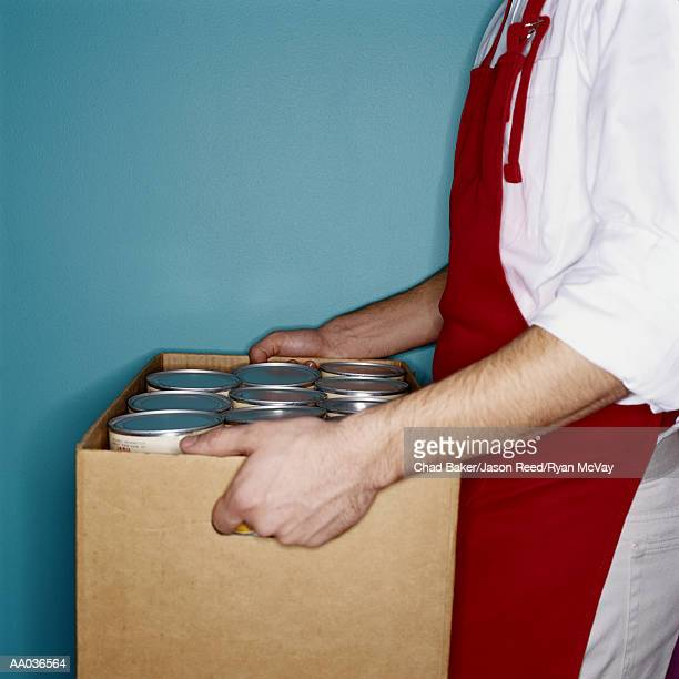 Clerk carrying box of canned goods, mid section, side view