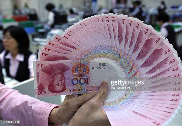 A clerk counts Chinese renminbi bills at a bank in Taipei on November 11 2010 World leaders on November 11 start two days of summit talks dominated...
