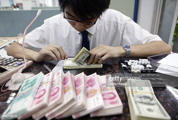 CHINA A clerk counts stacks of Chinese yuan and US dollars at a bank July 22 2005 in Shanghai China The People's Bank of China the central bank...