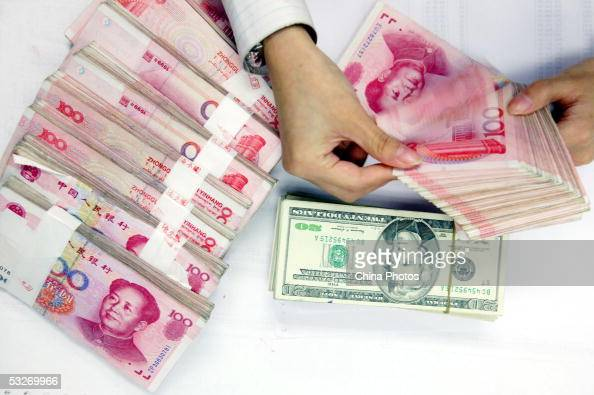 A clerk counts stacks of Chinese yuan and US dollars at a bank on July 22 2005 in Shanghai China The People's Bank of China the central bank...