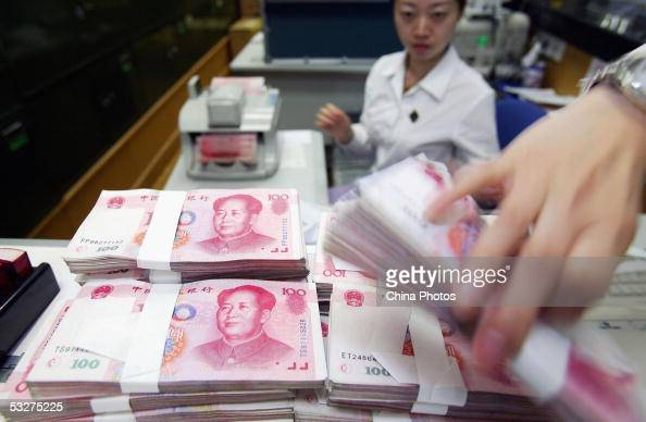 A clerk counts stacks of Chinese yuan at a bank on July 22 2005 in Shanghai China The People's Bank of China the central bank announced to scrap the...