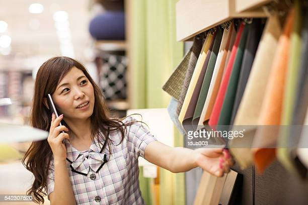 Clerk looking at fabric samples while talking on smartphone