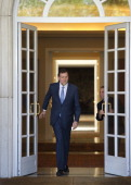 A clerk opens the door of the Moncloa palace for Spanish Prime Minister Mariano Rajoy walking out to welcome his Italian counterpart Prime Minister...