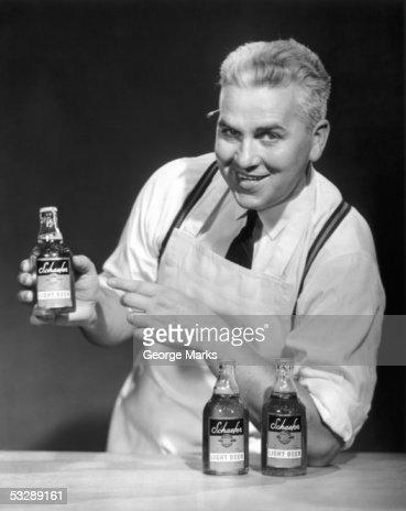 Clerk pointing to bottle of beer : Foto de stock