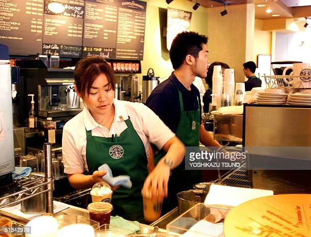 Clerks of a Starbucks Coffee store in Tokyo prepare orders as Starbucks Coffee Japan celebrates its fifth anniversary 02 August 2001 the first and...
