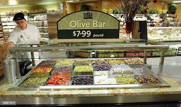 A clerks prepares the kiosk with many types of olives as Whole Foods Market readies for its opening February 5 2004 in New York City The market...