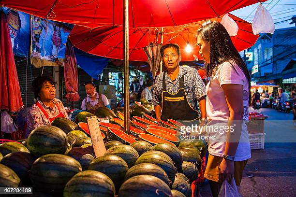 Clerks selling fresh watermelon for customer at the market