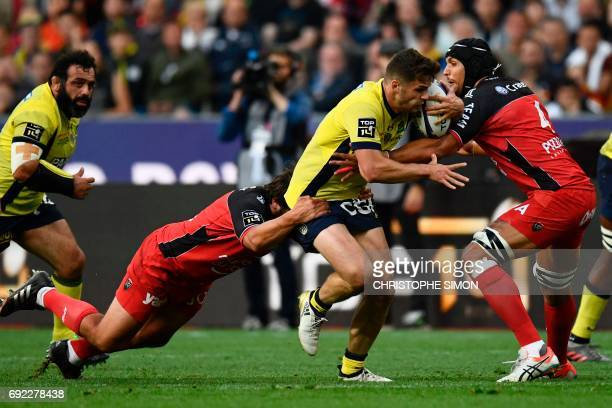 Clermont's centre Damien Penaud is tackled by Toulon's lock Juandre Kruger during the French Top 14 rugby union final match Clermont vs Toulon on...
