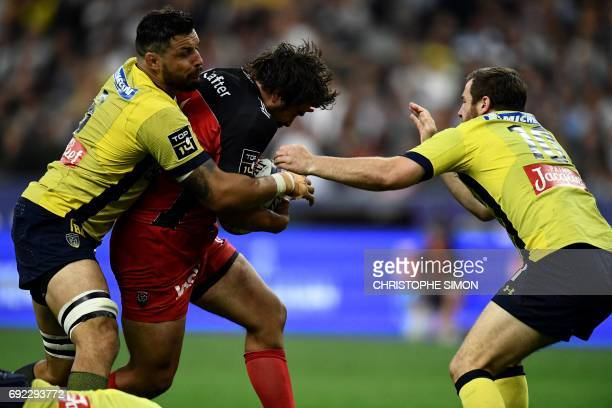 Clermont's centre Remi Lamerat is tackled by Clermont's flanker Damien Chouly during the French Top 14 rugby union final match Clermont vs Toulon on...