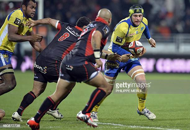 Clermont's French flanker Julien Bonnaire breaks away from Lyon's players during the French Top 14 rugby union match between Lyon vs Clermont on...