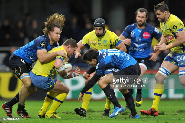 Clermont's French hooker Benjamin Kayser is tackled by Montpellier's French flyhalf François TrinhDuc and Montpellier's South African flanker Wiaan...