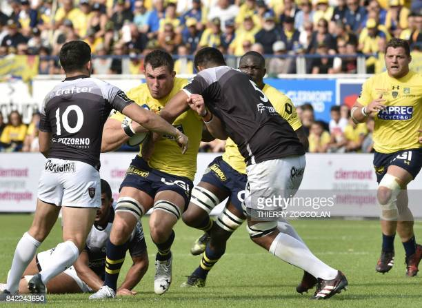 Clermont's French lock Paul Jedrasiak is tackled by RC Toulon's French lock Romain Taofifenua and RC Toulon's French flyhalf Anthony Belleau during...