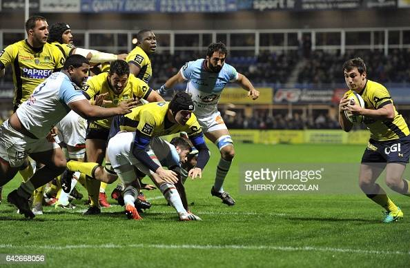 TOPSHOT Clermont's French scrumhalf Charlie Cassang catches the ball before scoring a try during the French Top 14 rugby union match ASM Clermont vs...