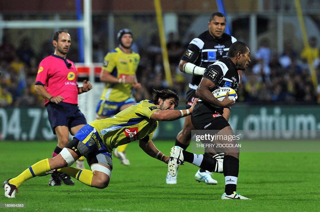 Clermont's French scrum-half Ludovic Radosavljevic (L) tries to tackle Brive's Fidji winger Elia Radikedike (R) during the French Top 14 rugby Union match between ASM Clermont Auvergne and CA Brive on October 26, 2013 at the Marcel Michelin stadium in Clermont-Ferrand.