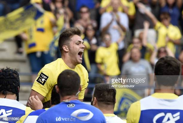 Clermont's French winger Damian Penaud celebrates with teammates after scoring a try during the French Top 14 rugby union match ASM Clermont vs...
