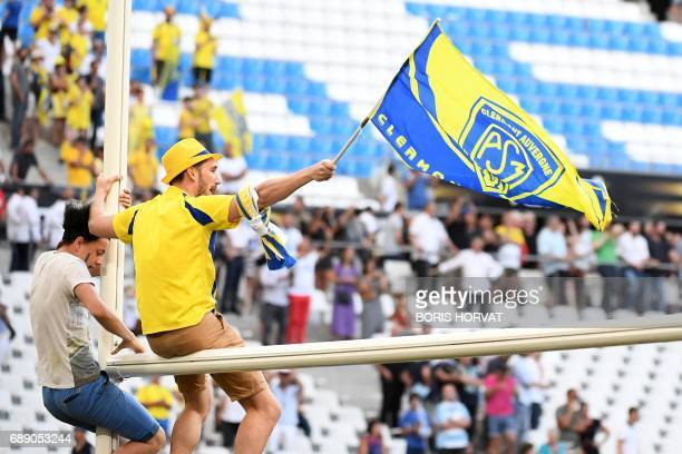 Clermont's supporters climb the goal posts and wave flags after the French Top 14 rugby union semifinal match between Racing 92 and ClermontFerrand...