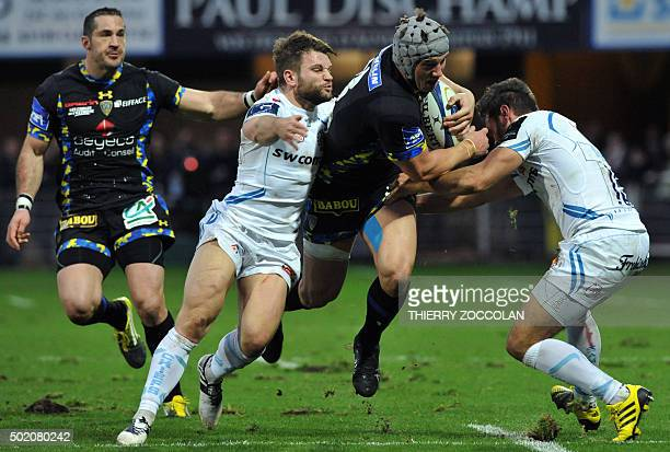 Clermont's Welsh centre Jonathan Davies is tackled during the European Rugby Champions Cup rugby union match between Clermont and Exeter at the...