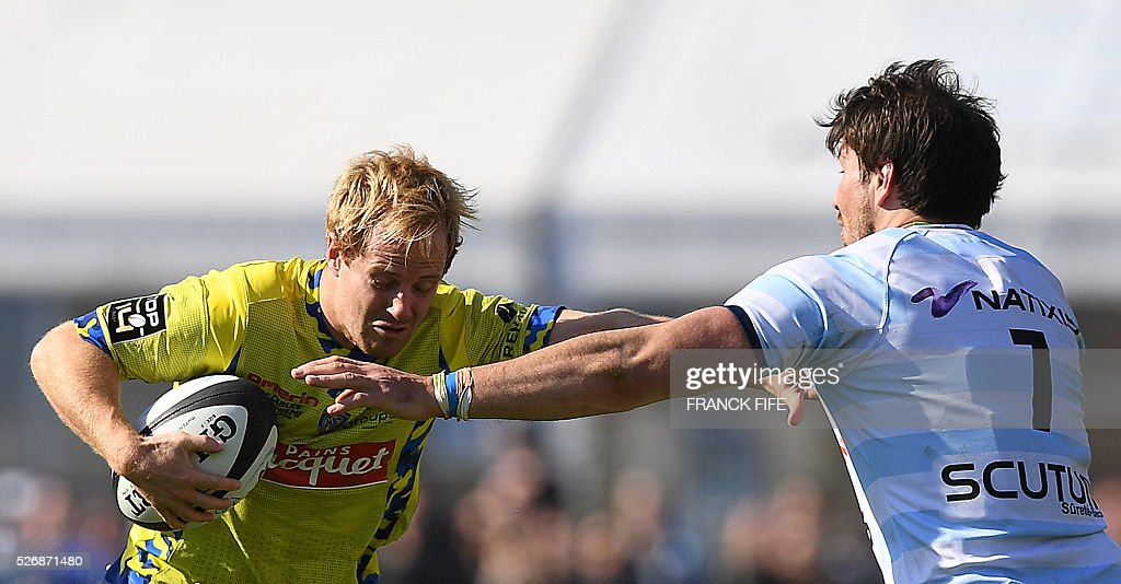 Clermont's Welsh centre Jonathan Davies runs with the ball as Racing 92 French back row Thibault Dubarry (R) tries to block him during the French Top 14 rugby union match between Racing 92 vs Clermont at Yves du Manoir stadium in Colombes on May 1, 2016. / AFP / FRANCK