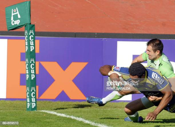 Clermont's Winger Nalaga Napolioni scores a try tackled by Montauban's Dalla Riva Johan during the European 'HCup' rugby union match Montauban vs...