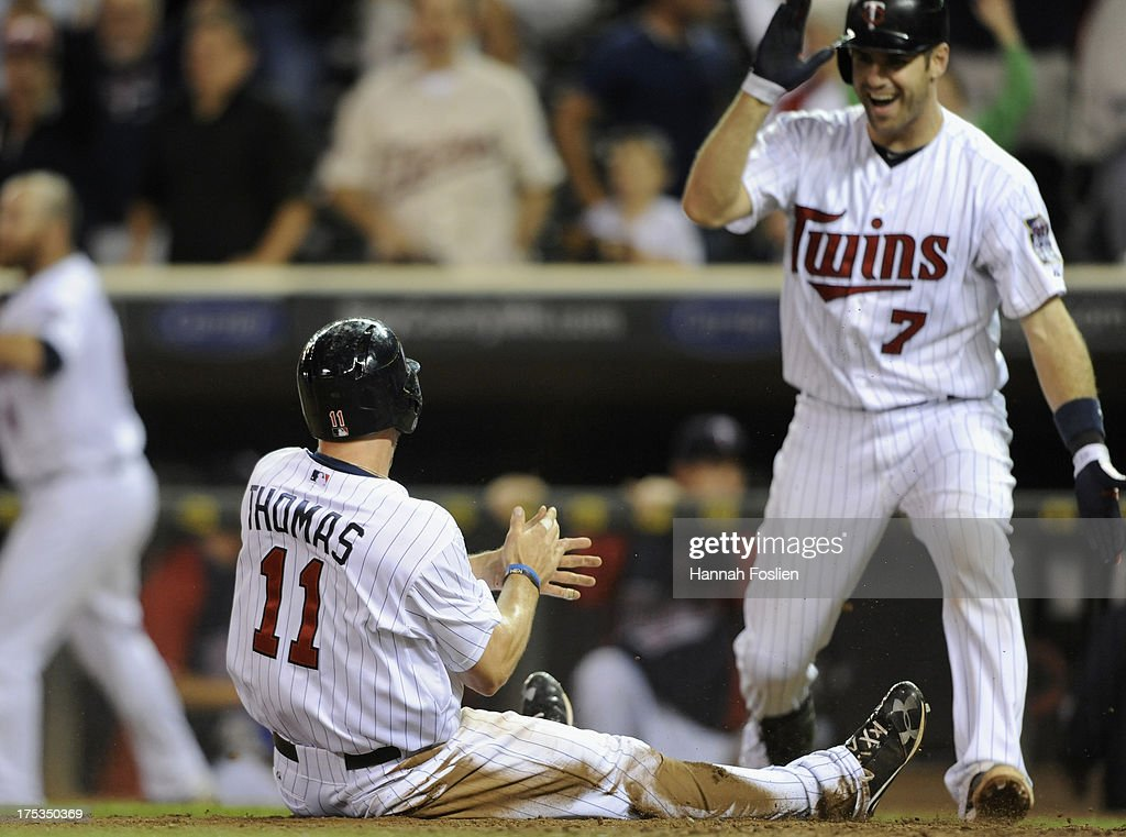 <a gi-track='captionPersonalityLinkClicked' href=/galleries/search?phrase=Clete+Thomas&family=editorial&specificpeople=4952485 ng-click='$event.stopPropagation()'>Clete Thomas</a> #11 of the Minnesota Twins celebrates as he slides across home plate scoring the winning run as <a gi-track='captionPersonalityLinkClicked' href=/galleries/search?phrase=Joe+Mauer&family=editorial&specificpeople=214614 ng-click='$event.stopPropagation()'>Joe Mauer</a> #7 looks on during the thirteenth inning of the game against the Houston Astros on August 2, 2013 at Target Field in Minneapolis, Minnesota. The Twins defeated the Astros 4-3 in thirteen inning.