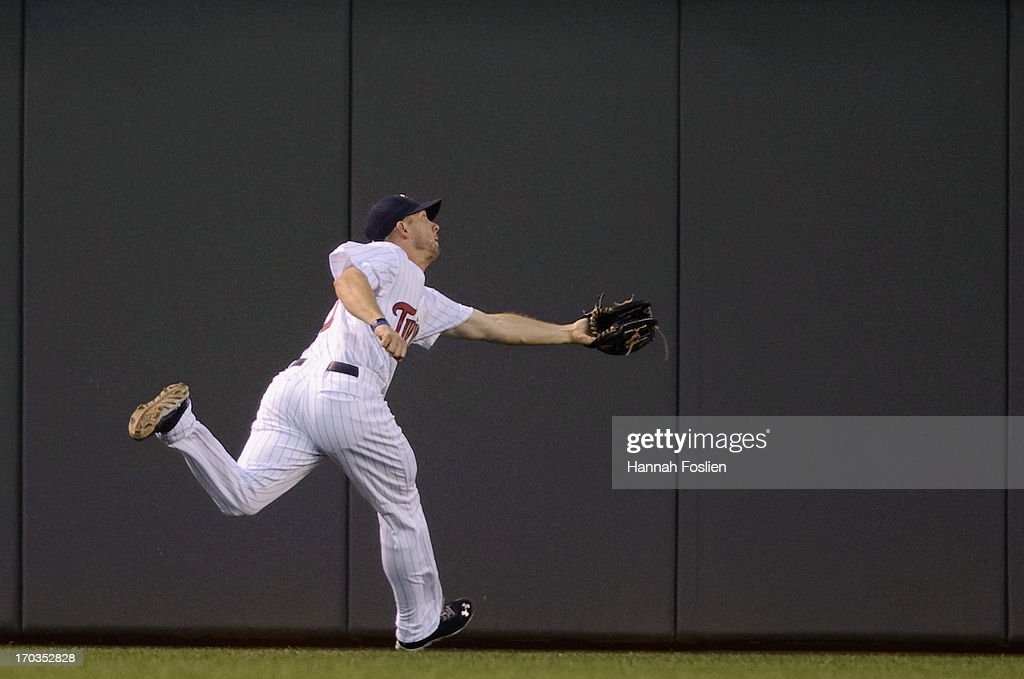 Clete Thomas #11 of the Minnesota Twins makes a catch in center field during the seventh inning of the game against the Philadelphia Phillies on June 11, 2013 at Target Field in Minneapolis, Minnesota. The Twins defeated the Phillies 3-2.
