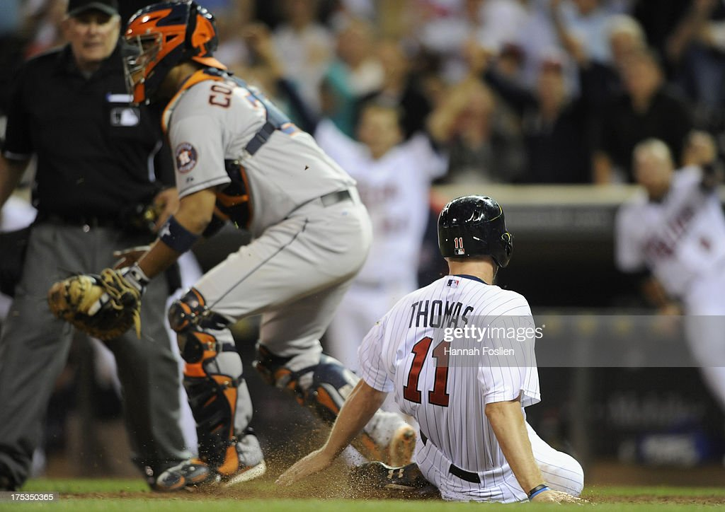 <a gi-track='captionPersonalityLinkClicked' href=/galleries/search?phrase=Clete+Thomas&family=editorial&specificpeople=4952485 ng-click='$event.stopPropagation()'>Clete Thomas</a> #11 of the Minnesota Twins slides safely as <a gi-track='captionPersonalityLinkClicked' href=/galleries/search?phrase=Carlos+Corporan&family=editorial&specificpeople=5716887 ng-click='$event.stopPropagation()'>Carlos Corporan</a> #22 of the Houston Astros defends home plate during the thirteenth inning of the game on August 2, 2013 at Target Field in Minneapolis, Minnesota. The Twins defeated the Astros 4-3 in thirteen inning.