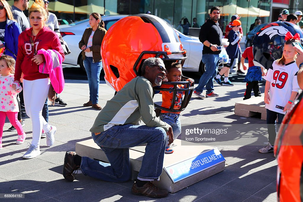 A Cleveland Browns fan and his young son pose in a large Cleveland Browns Helmet outside the NFL Experience at the George R. Brown Convention Center on January 29, 2017, in Houston, Texas.