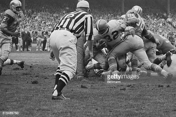 Cleveland Browns fullback Jim Brown fights his way over the goal line for a second quarter score in game against Detroit Lions Lions defensive end...