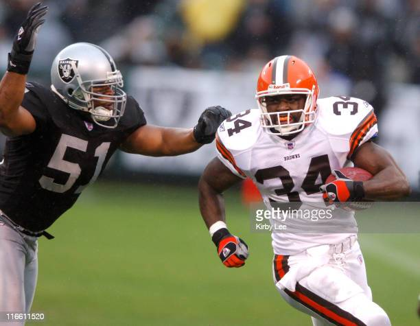 Cleveland Browns running back Reuben Droughns tries to elude Oakland Raiders linebacker Tim Johnson in the first quarter of 96 victory at McAfee...