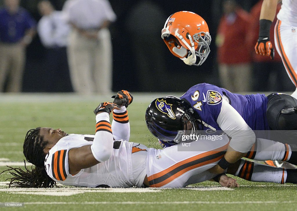 Cleveland Browns wide receiver Josh Cribbs is separated from his helmet and the ball by Baltimore Ravens long snapper Morgan Cox resulting in a...