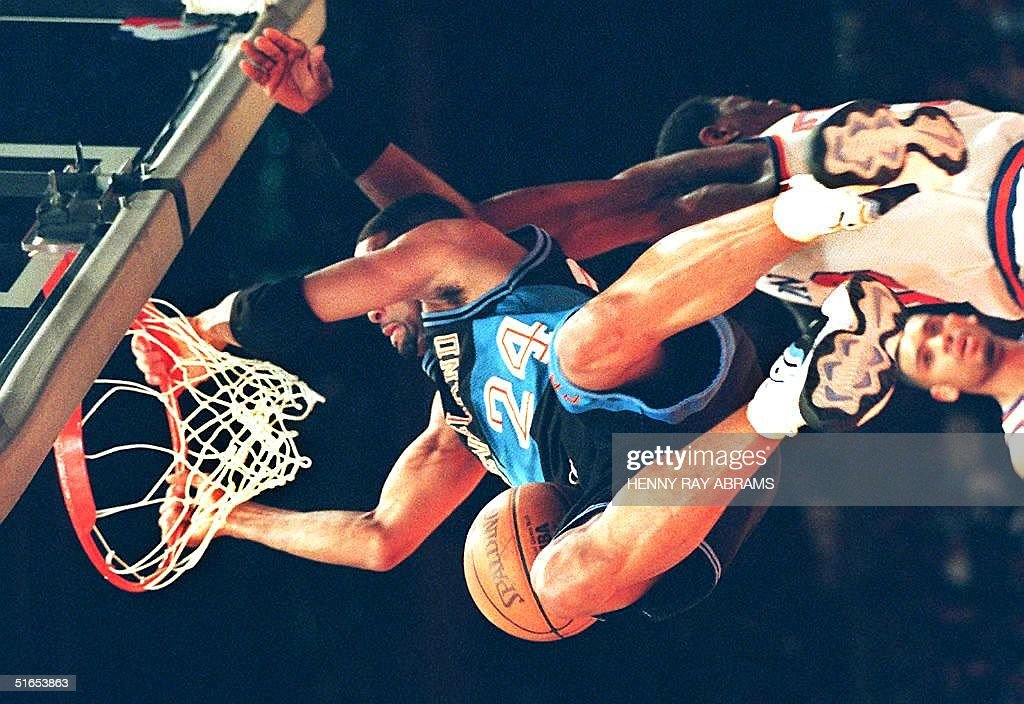 Cleveland Cavaliers' Chris Mills hangs on to the rim after dunking for two points over the New York Knicks' Patrick Ewing at the end of the first...