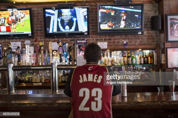 Cleveland Cavaliers fan wearing a Lebron James jersey watches news coverage of LeBron James return to Cleveland at Panini's Bar and Grille in...
