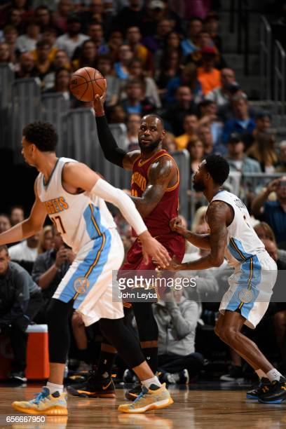 Cleveland Cavaliers forward LeBron James holds the ball up away from Denver Nuggets guard Will Barton during the second quarter on March 22 2017 in...