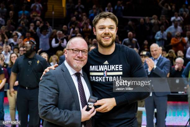 Cleveland Cavaliers general manager David Griffin presents former Cavalier Matthew Dellavedova of the Milwaukee Bucks his championship ring prior to...