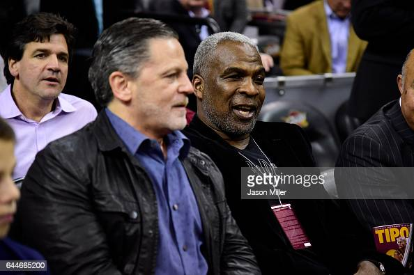Cleveland Cavaliers owner Dan Gilbert sits next to former NBA player Charles Oakley prior to the game between the Cleveland Cavaliers and the New...